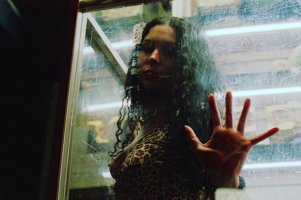 Straßenfotografie: Eine Frau mit geöffnetem Oberteil drückt ihre Hand an eine Scheibe.