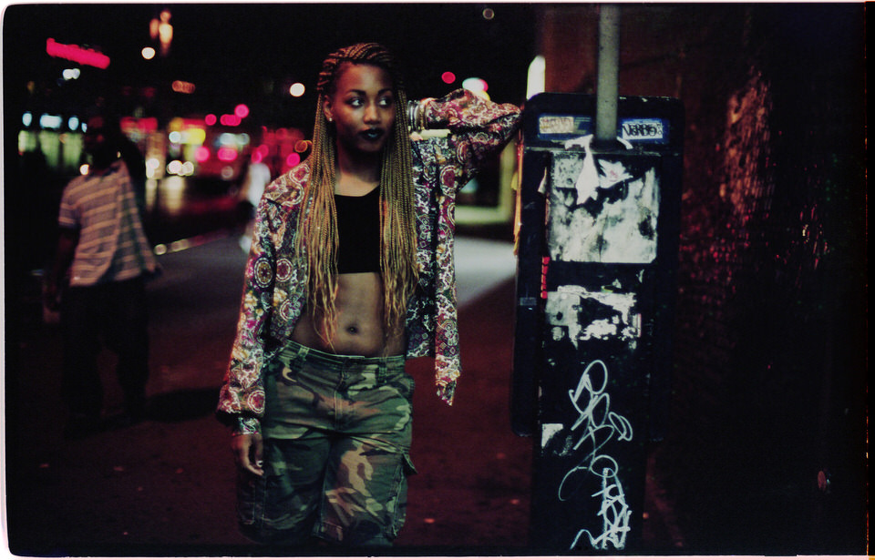 Straßenfotografie: Eine Frau mit langen Haaren lehnt sich an eine Telefonzelle an.