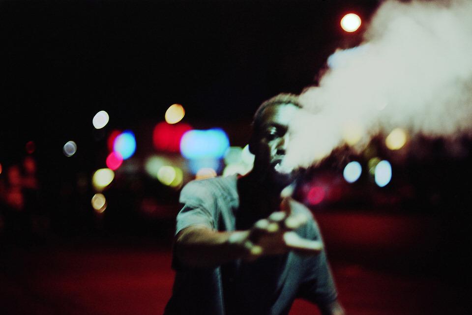 Straßenfotografie: Ein Mann lässt Rauch aus seinem Mund aufsteigen.