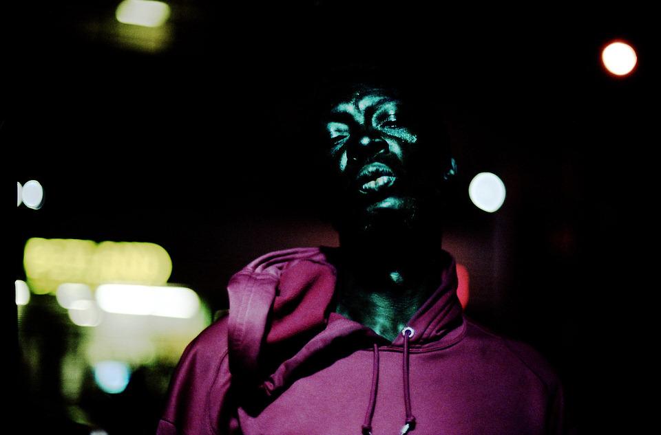 Straßenfotografie: Portrait einer Person, die ihre Augen halb geschlossen hält.