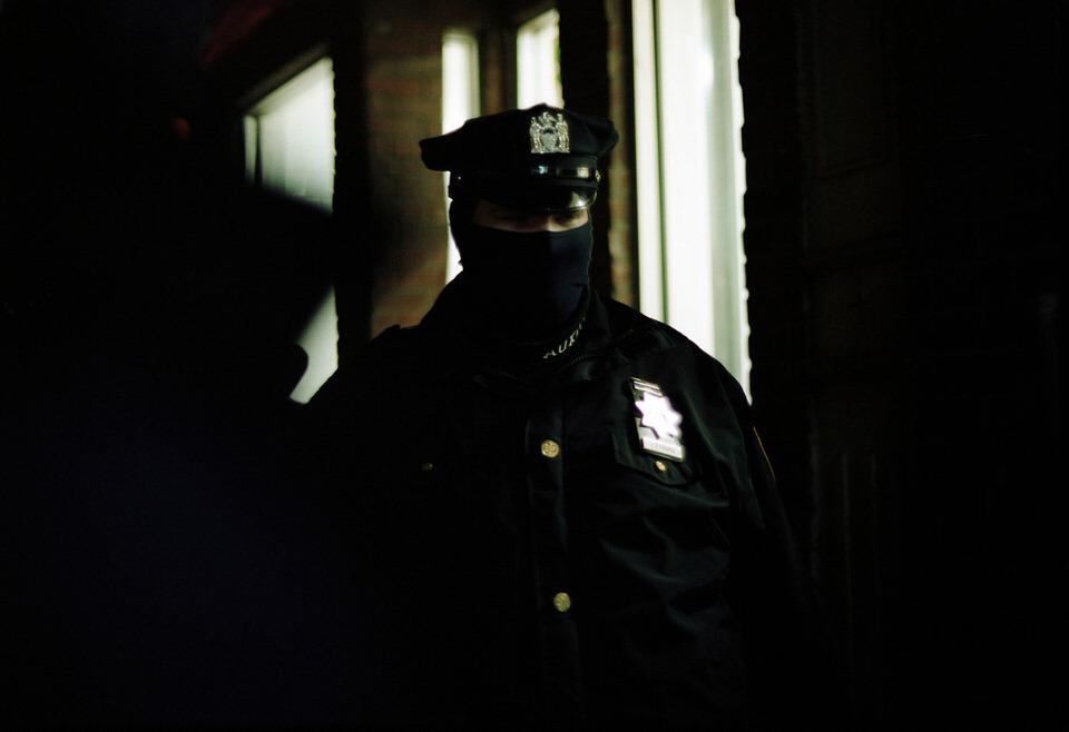 Straßenfotografie: Ein Polizist, der sein Halstuch über die Nase gezogen hat.