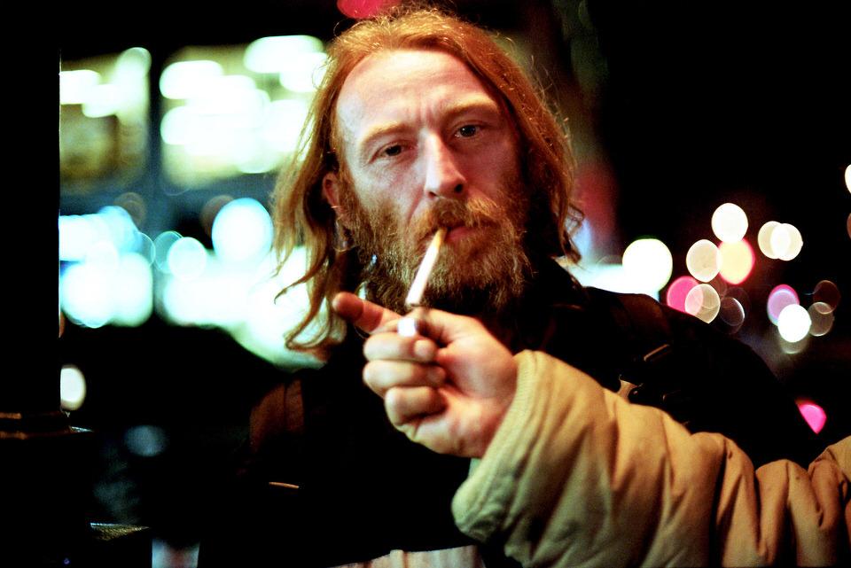 Straßenfotografie: Ein Mann bekommt von jemandem Feuer für die Zigarette und starrt dabei in die Kamera.