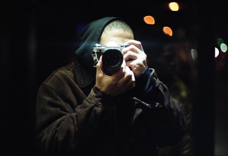 Straßenfotografie: Der Fotograf mit Kamera fotografiert sich selbst im Spiegel.