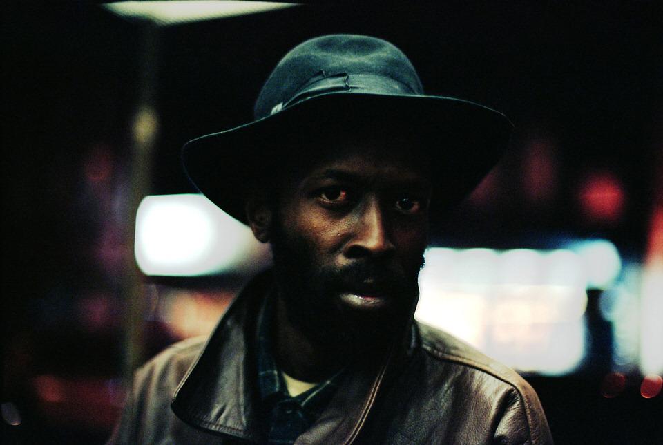 Straßenfotografie: Ein Mann mit Hut schaut in die Kamera.