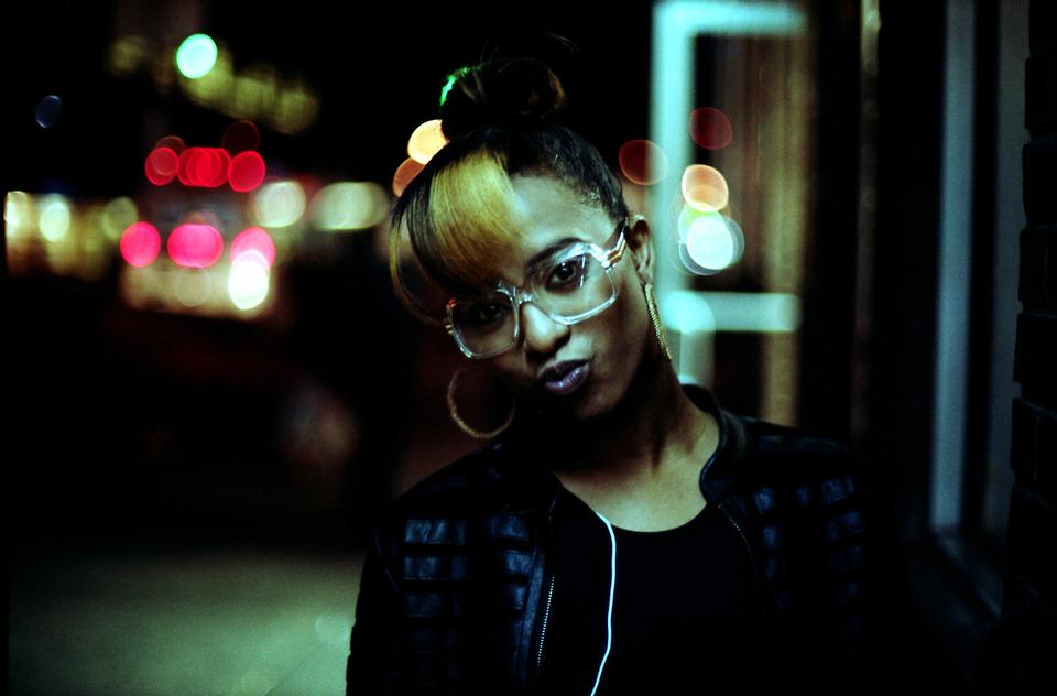 Straßenfotografie: Eine Frau mit Brille sieht in die Kamera, im Hintergrund verschwommene Stadt.