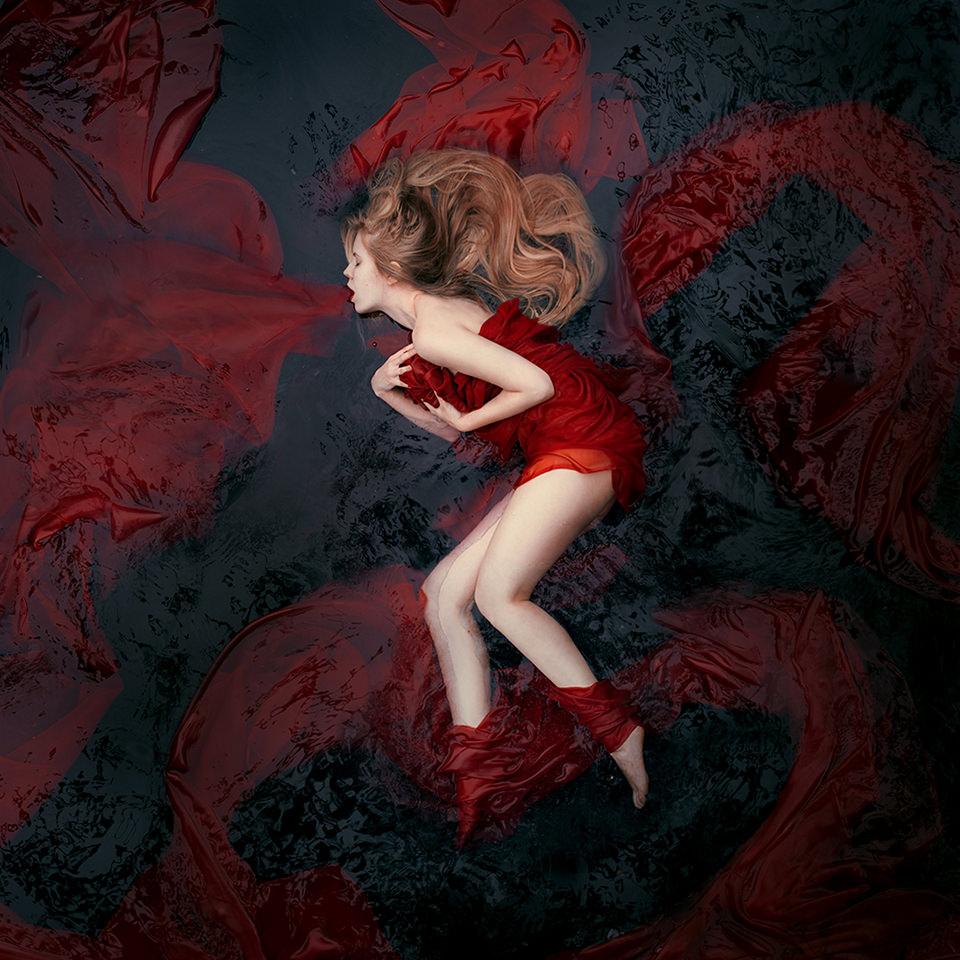 Eine Frau liegt im Wasser. Aus ihrem Mund quillt ein rotes Tuch, das um sie herum schwimmt.
