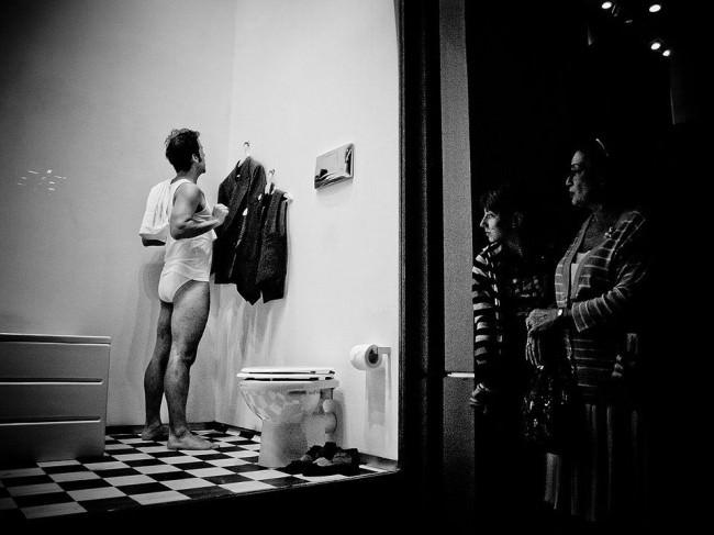 Ein Mann steht in einem Schaufenster vor einem Spiegel
