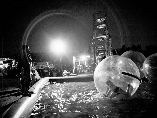 In einem Freizeitpark sind Menschen in Plastikblasen auf einem Pool