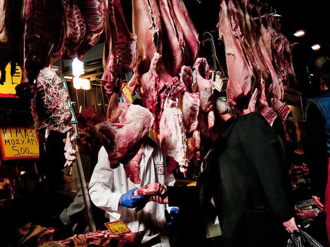 Ein Mann steht auf der Straße zwischen Fleisch an einem Metzgerstand