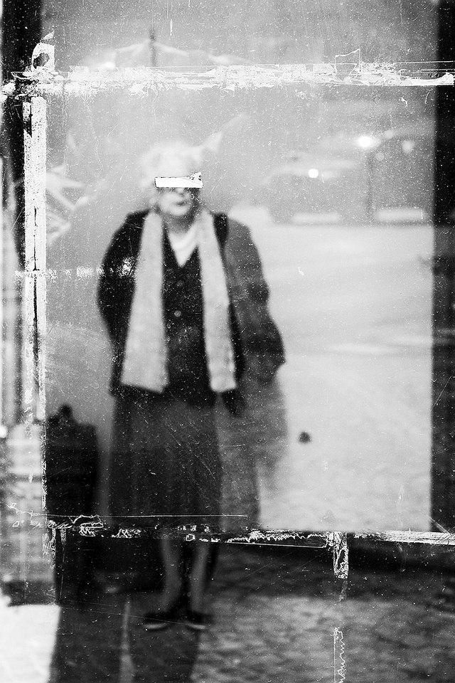 Eine alte Frau hinter einer dreckigen Scheibe.