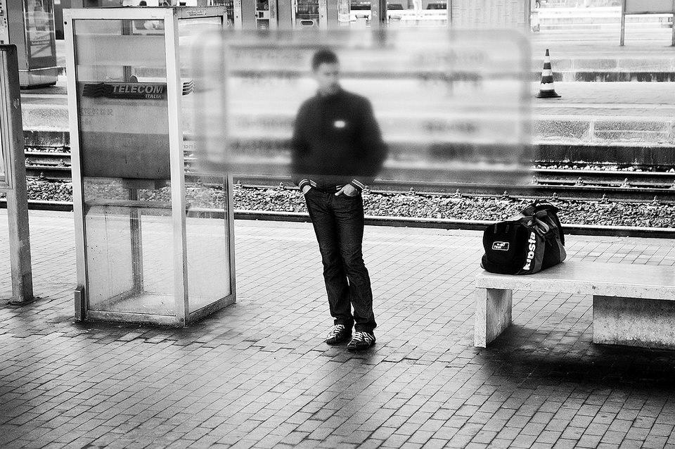 Ein Mann steht an einer Haltestelle.