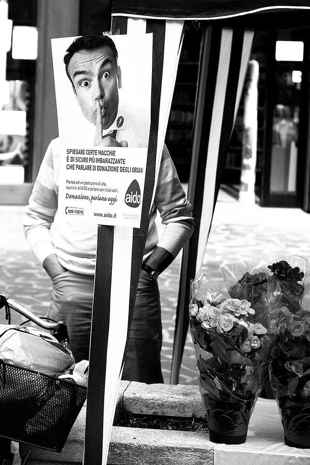 Ein Mann hinter einem Schild an einem Blumenstand.