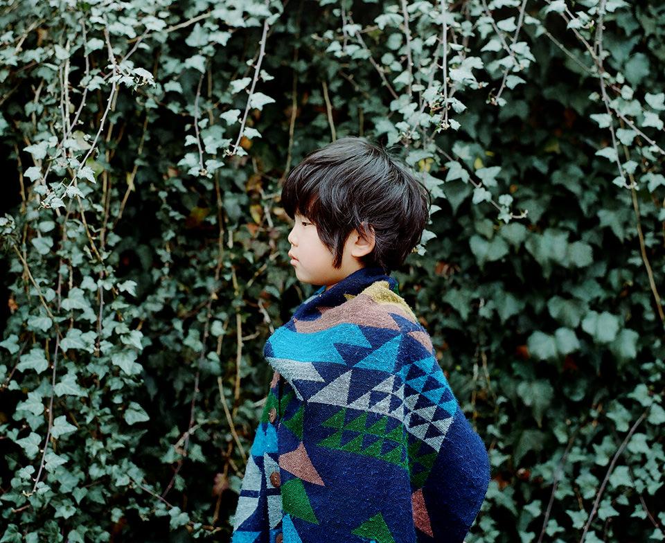 Ein Kind ist in eine Decke gehüllt und steht im Profil vor einer Efeuhecke.