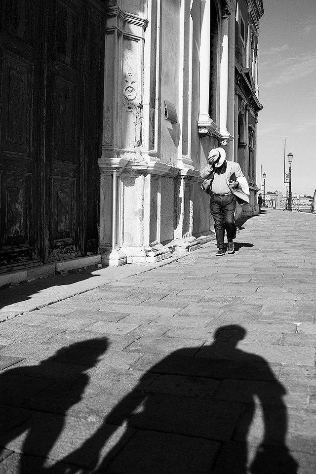 Ein Mann mit Hut und zwei Schatten.