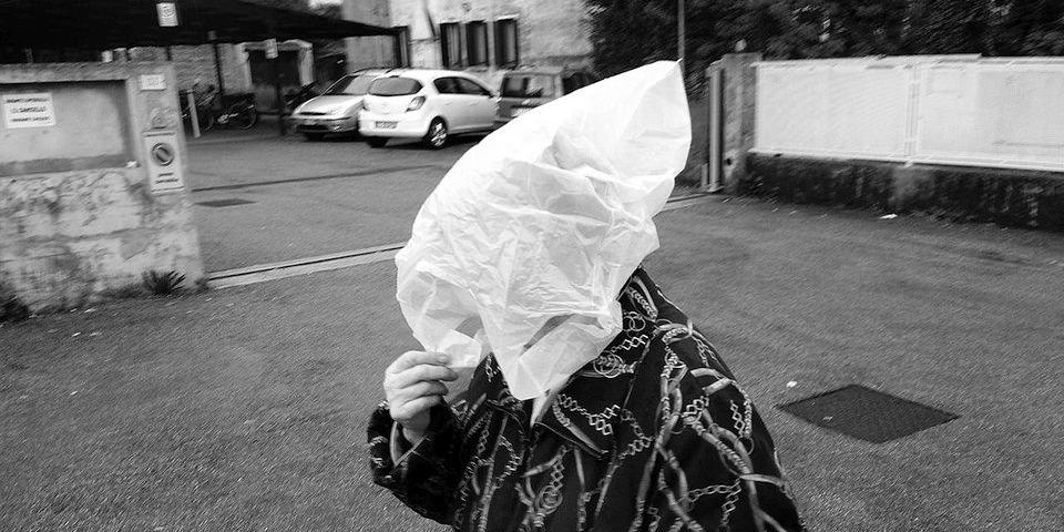 Eine Frau hat eine weiße Plastiktüte auf dem Kopf.