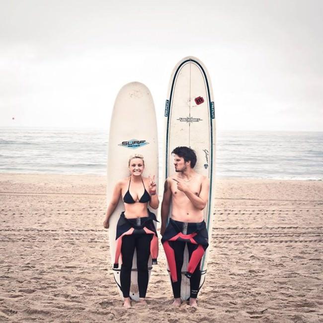 Zwei Menschen stehen am Strand mit ihren Surfbrettern hinter sich