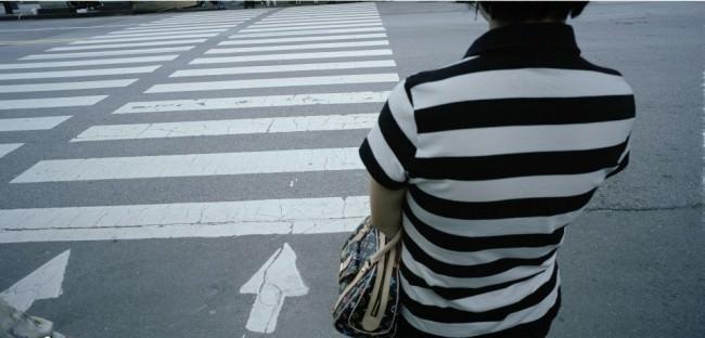 Eine Frau in gestreiftem Shirt vor einem Zebrastreifen.