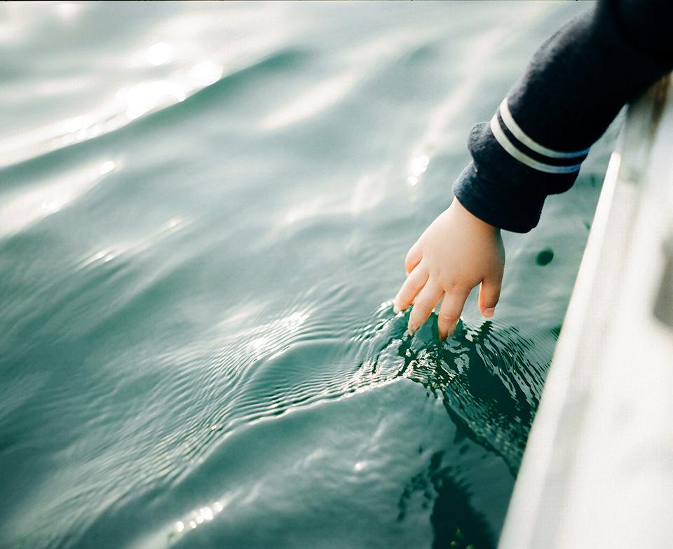 Eine Kinderhand greift ins Wasser.