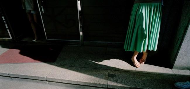 Eine Frau in grünem Kleid im Schatten.