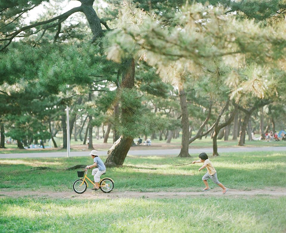 Ein Kind fährt Fahrrad, ein zweites rennt hinter ihm her.
