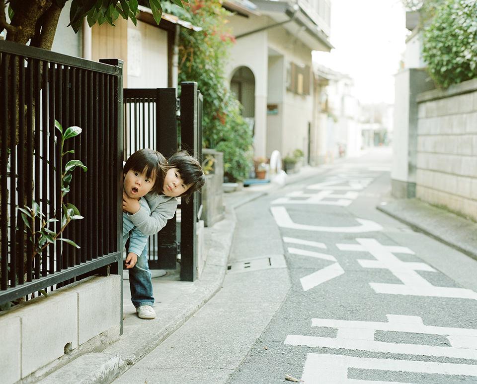 Zwei Kinder sehen vorsichtig aus einer Einfahrt heraus.