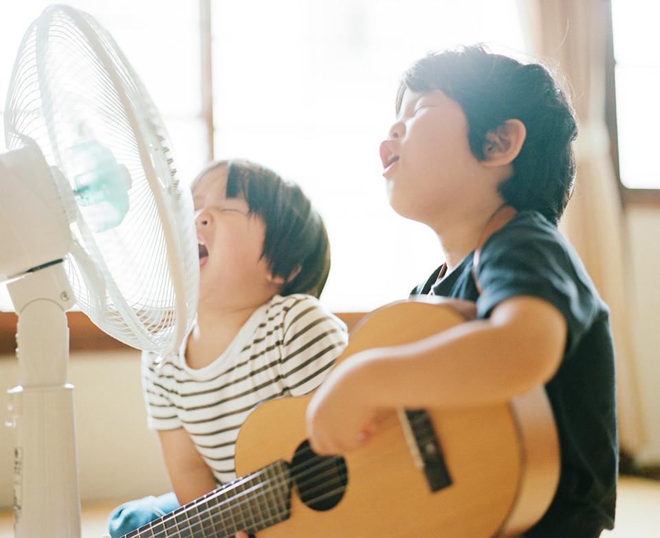 Zwei Kinder sitzen vor einem Ventilator und singen. Ein Kind hält eine Gitarre in der Hand.