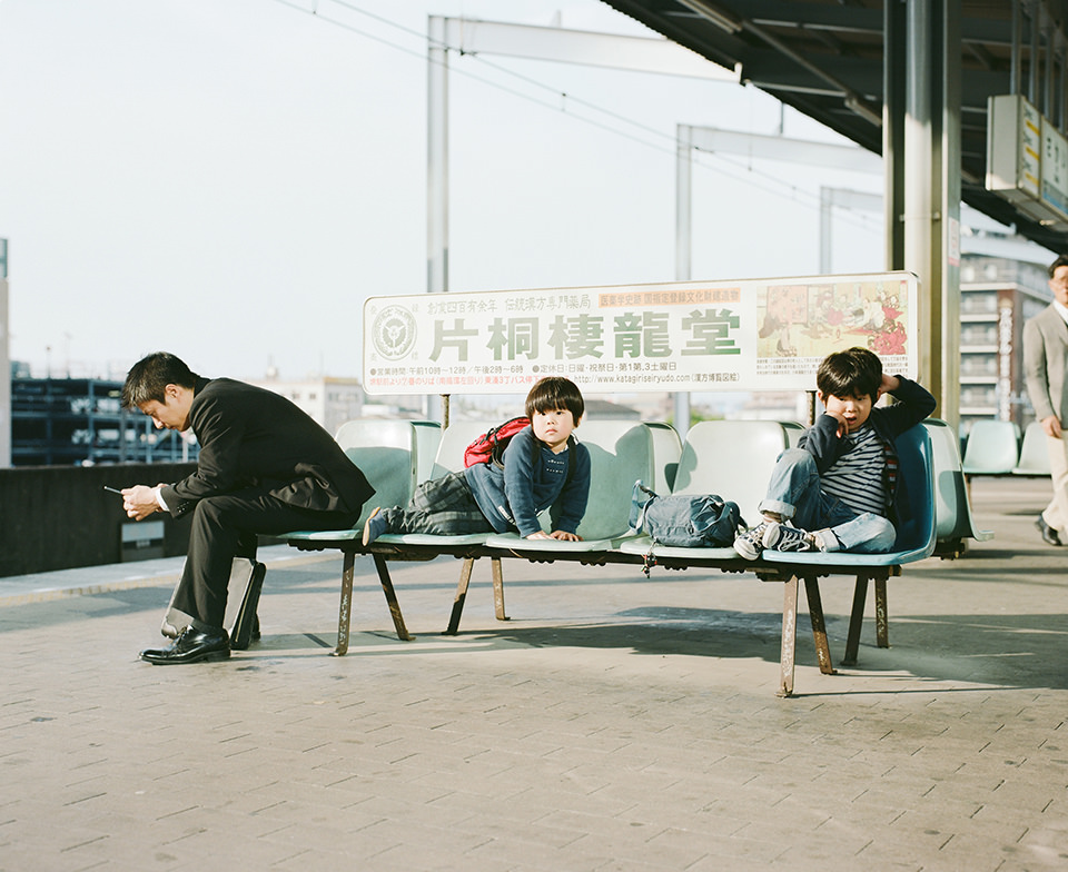 Zwei Kinder und ein Mann sitzen auf einer Bank.