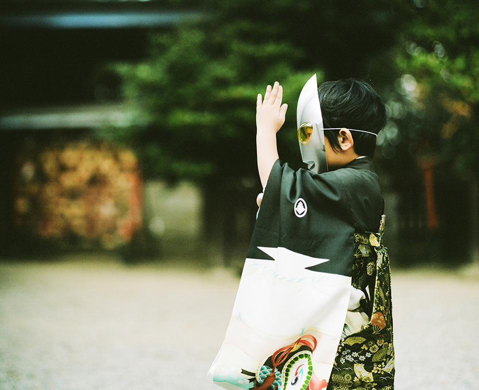 Ein Kind mit Maske im Profil hebt die Hand.