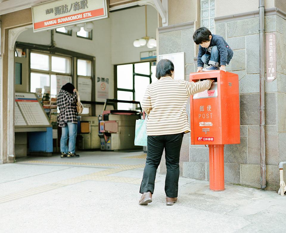 Ein Kind hockt auf einem Briefkasten, in den eine Frau gerade einen Brief gibt.