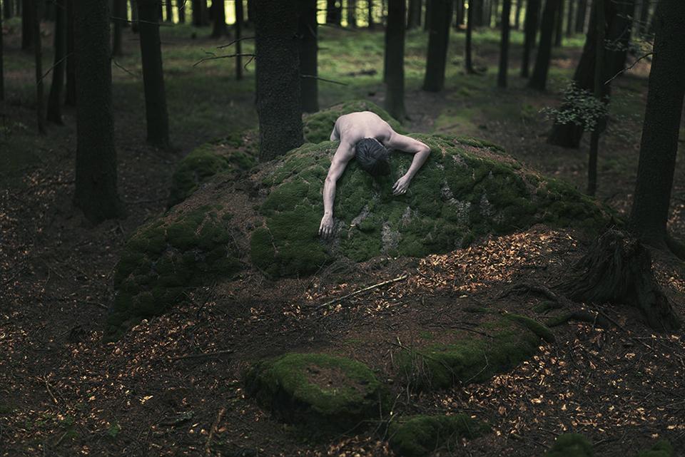Ein Oberkörper hängt über einen Stein