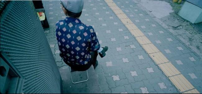 Ein Mann mit gemustertem Shirt auf der Straße.