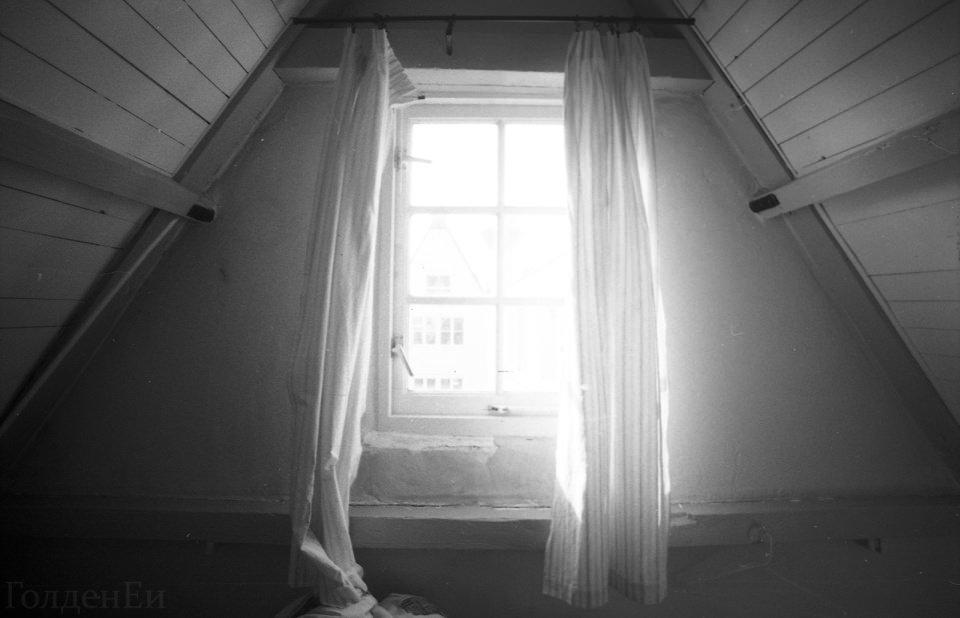 Sonnenlicht scheint grell durch ein Fenster mit Vorhängen auf einem Spitzboden.