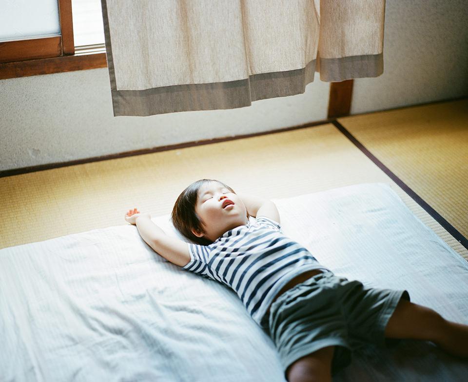 Ein Kind schläft auf einer Matte unter dem Fenster.