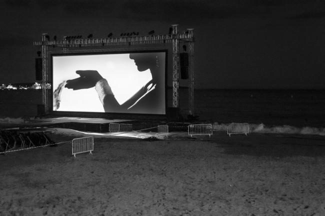 Eine Kinoleinwand, die draußen im Dunkeln aufgestellt ist.