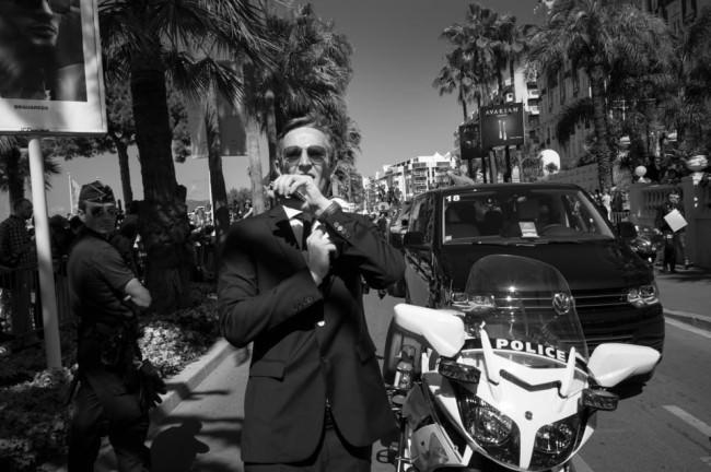 Ein Sicherheitsbeamter mit Sonnenbrille spricht per Funkarmband mit jemandem.