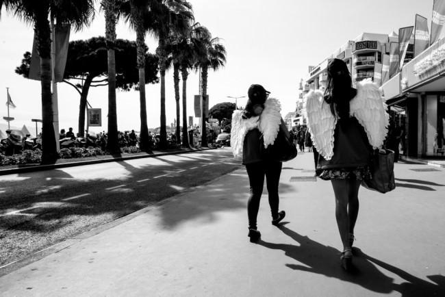 Zwei Frauen mit Engelsflügeln gehen eine Straße entlang.