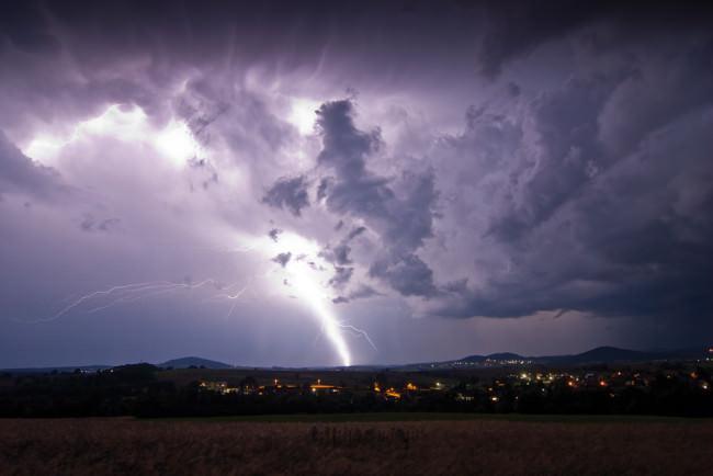 Ein Blitz schlägt in eine Landschaft ein.