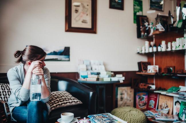Frau sitzt an einem Kaffeetisch in einer Sofaecke
