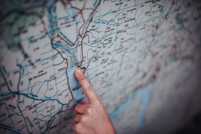 Finger zeigt auf eine Landkarte