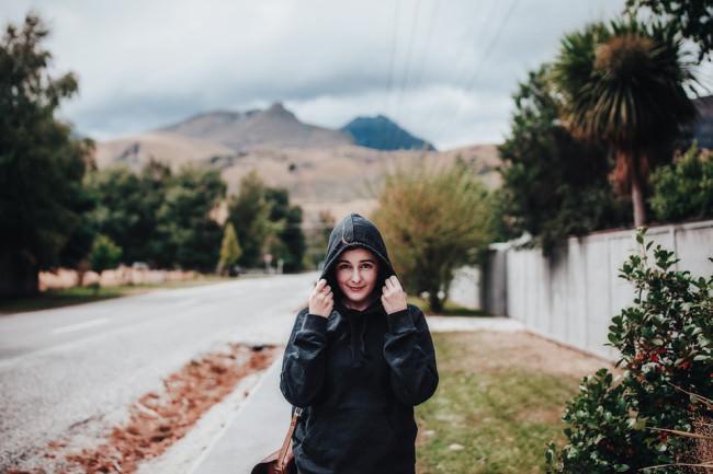 Mädchen zieht sich vor einer Berglandschaft die Kapuze über den Kopf
