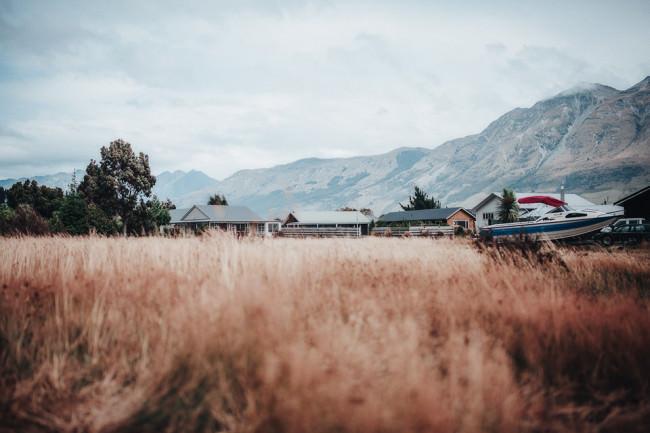 Feld vor einigen Hütten vor einer Berglandschaft
