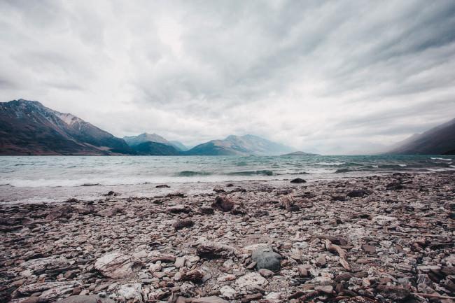 Steinküste eines Sees vor einer Berglandschaft