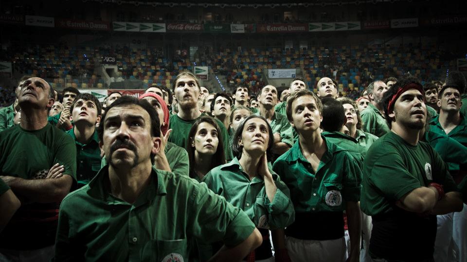Menschen in grün gekleidet sehen gespannt nach oben.