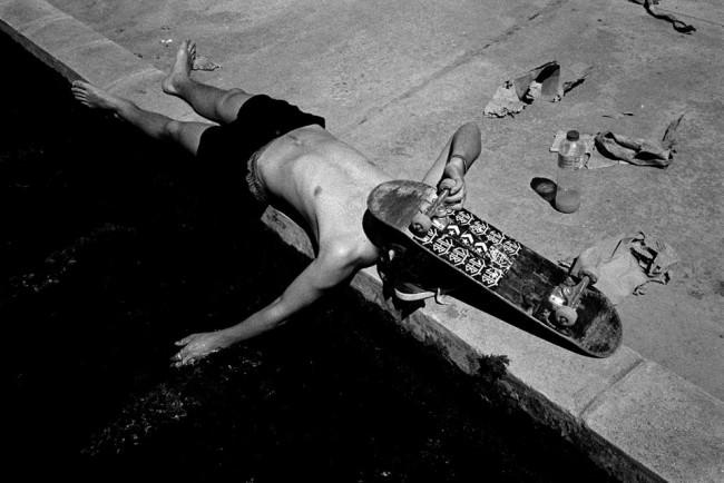 Skater mit freiem Oberkörper liegt auf dem Boden und hält eine Hand ins Wasser.