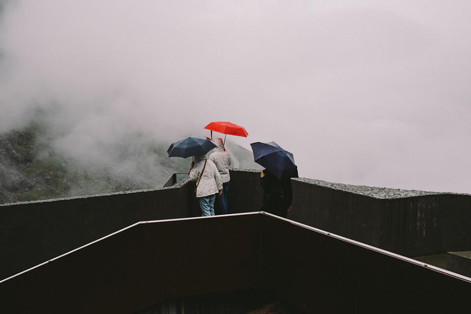 Drei Menschen stehen mit Regenschirmen über eine Brüstung gebeugt.