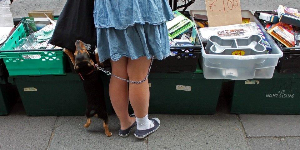 Ein Hund steht mit seiner Besitzerin an einem Flohmarktstand.