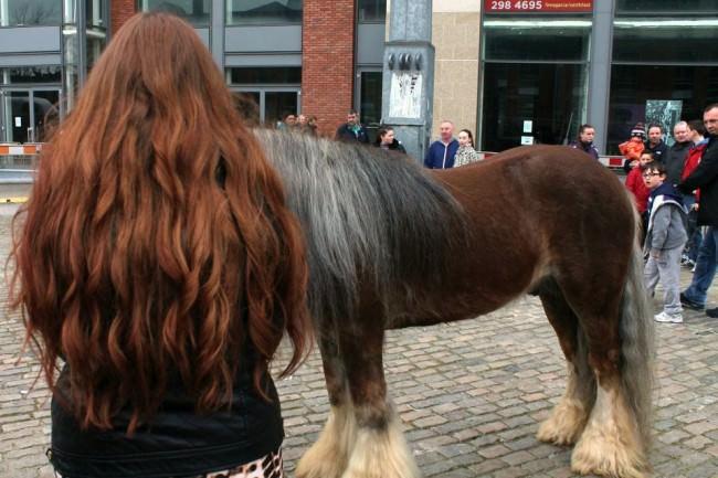 Eine langhaarige Frau und ein Pferd.