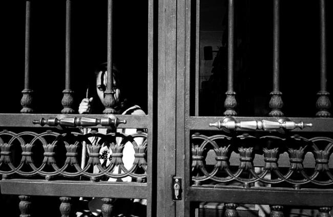Eine Frau steht hinter einem fein verzierten Tor und schaut in die Kamera.