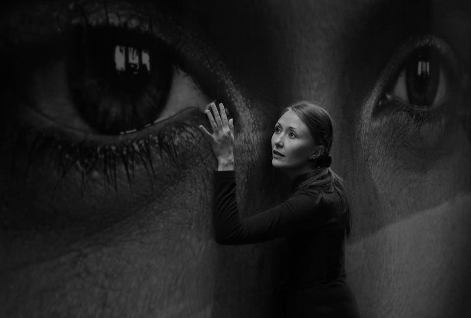 Frau vor Plakat mit Auge