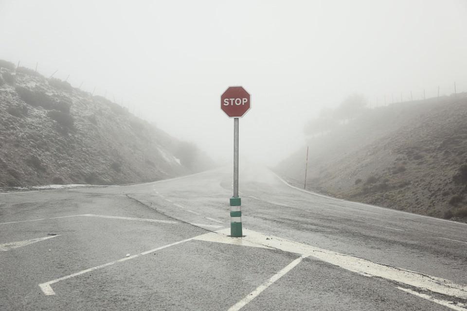 Ein Stopp-Schild auf einer leeren Straße vor dichtem Nebel.